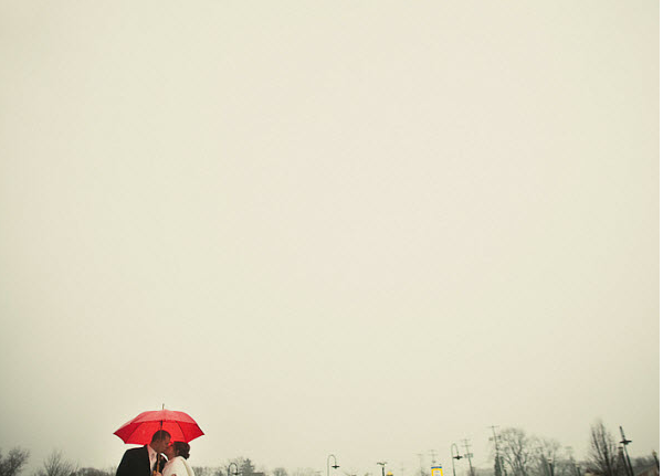 bride and groom at January wedding with red umbrella